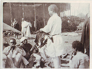 "Ethiopian soldiers. A ""tukul"" from mud of octagonal shape is visible in the background. The text on the back is in French and it reads as follows: Ethiopian soldiers eating raw meat. The photograph was taken by the Seljan brothers."